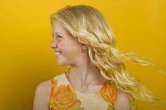 Schönes blondes Mädchen auf einem gelben Hintergrund Lizenzfreie Stockfotografie