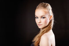 Schönes blondes Mädchen auf einem schwarzen Hintergrund stockbild