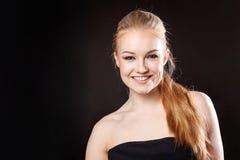 Schönes blondes Mädchen auf einem schwarzen Hintergrund Stockfotografie