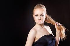 Schönes blondes Mädchen auf einem schwarzen Hintergrund Stockbilder