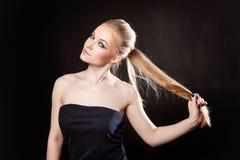 Schönes blondes Mädchen auf einem schwarzen Hintergrund Lizenzfreies Stockbild