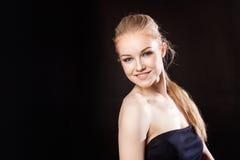 Schönes blondes Mädchen auf einem schwarzen Hintergrund Stockfoto