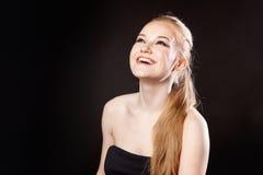 Schönes blondes Mädchen auf einem schwarzen Hintergrund Lizenzfreies Stockfoto