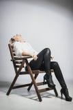 Schönes blondes Mädchen auf einem Stuhl Lizenzfreies Stockbild