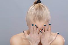 Schönes blondes Mädchen bedeckt ihr Gesicht mit den Händen verzweiflung Stockbilder