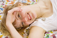 Schönes blondes Mädchen, das auf Bett und dem Lächeln liegt Lizenzfreie Stockbilder
