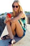 Schönes blondes Mädchen, das auf dem Dach mit Handy sitzt Stockfotografie