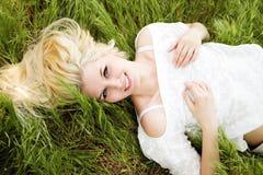 Schönes blondes Mädchen, das auf dem grünen Gebiet liegt Lizenzfreie Stockbilder