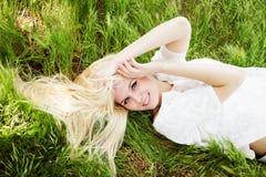 Schönes blondes Mädchen, das auf dem grünen Gebiet liegt Stockbilder