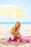Schönes blondes Mädchen, das auf dem Strand sitzt Stockbilder