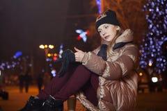 Schönes blondes Mädchen, das auf Hintergrund mit Lichtern auf dem s sitzt Lizenzfreie Stockfotografie