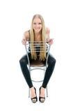 Schönes blondes Mädchen, das auf Stuhl sitzt Stockfotos