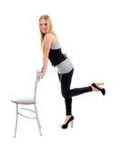 Schönes blondes Mädchen, das auf Stuhl sitzt Stockfotografie