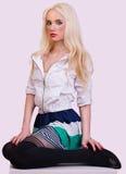 Schönes blondes Mädchen, das auf Stuhl sitzt Stockbilder