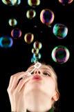 Schönes blondes Mädchen, das bunte Seifenluftblasen bildet Lizenzfreies Stockfoto