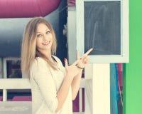 Schönes blondes Mädchen, das Daumen oben auf einem Brett im Freien zeigt Lizenzfreie Stockbilder