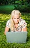Schönes blondes Mädchen, das draußen Laptop. verwendet. Stockfotografie