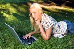 Schönes blondes Mädchen, das draußen Laptop. verwendet. Lizenzfreies Stockbild