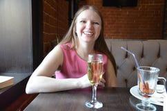 Schönes blondes Mädchen, das ein Glas Champagner oder Wein, trinkender Champagner in einem Restaurant, in einem glättenden rosa K stockbild