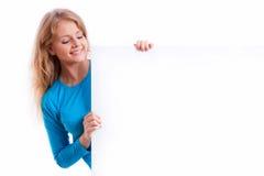 Schönes blondes Mädchen, das ein leeres weißes Brett hält Stockbild