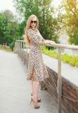 Schönes blondes Mädchen, das ein Leopardkleid und -Sonnenbrille trägt Stockbild