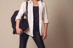 Schönes blondes Mädchen, das ein weißes Hemd mit einem ledernen Rucksack auf ihr zurück trägt stockfotografie