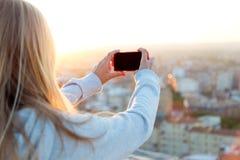 Schönes blondes Mädchen, das Fotos der Stadt macht Stockfotos