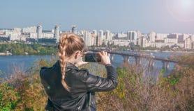 Schönes blondes Mädchen, das Fotos von der Stadt auf einem Smartphone macht Lizenzfreies Stockbild