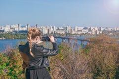 Schönes blondes Mädchen, das Fotos von der Stadt auf einem Smartphone macht Stockbild