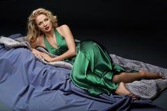 Schönes blondes Mädchen, das im grünen Kleid liegt Lizenzfreies Stockbild