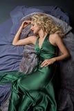 Schönes blondes Mädchen, das im grünen Kleid liegt Lizenzfreie Stockfotos
