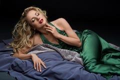 Schönes blondes Mädchen, das im grünen Kleid liegt Stockbilder