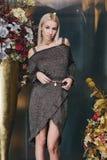 Schönes blondes Mädchen, das im grauen Kleid aufwirft Stockbild