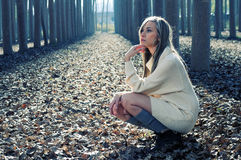 Schönes blondes Mädchen, das im Holz denkt Stockfotografie