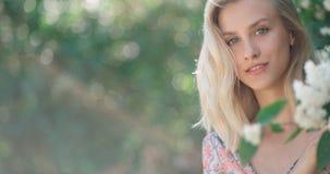 Schönes blondes Mädchen, das Kamera und das Lächeln betrachtet Stockbild