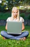 Schönes blondes Mädchen, das Laptop im Park. verwendet. Stockfotos