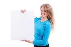 Schönes blondes Mädchen, das leeres weißes Brett zeigt Lizenzfreie Stockfotografie