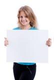 Schönes blondes Mädchen, das leeres weißes Brett zeigt Lizenzfreies Stockfoto