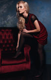 Schönes blondes Mädchen, das mit einem Stuhl in einem Kleid aufwirft Stockfoto