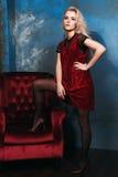Schönes blondes Mädchen, das mit einem Stuhl in einem Kleid aufwirft Stockbild