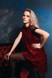 Schönes blondes Mädchen, das mit einem Stuhl in einem Kleid aufwirft Lizenzfreie Stockfotografie