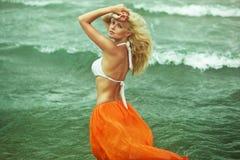 Schönes blondes Mädchen, das nahe dem Meer geht lizenzfreie stockfotos