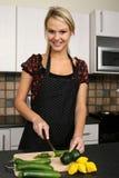 Schönes blondes Mädchen, das Nahrung zubereitet Stockbilder