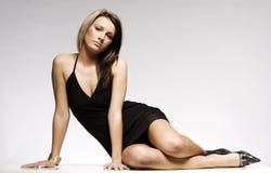 Schönes blondes Mädchen, das schwarzes Minikleid trägt Stockbilder