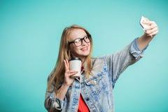 Schönes blondes Mädchen, das selfie mit Lächeln auf blauem Hintergrund nimmt Stockfotos