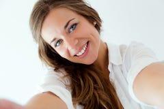 Schönes blondes Mädchen, das selfie nimmt Lokalisiert auf Weiß Lizenzfreie Stockfotografie