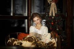 Schönes blondes Mädchen, das sitzende Entspannung mit warmer Decke auf Sofa nahe Weihnachtsbaum und dunklem Fenster sich umarmt stockbilder