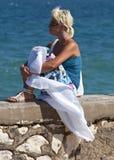 Schönes blondes Mädchen, das Sonne nahe Meer genießt Stockbilder