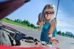 Schönes blondes Mädchen, das unter der Haube des Autos schaut lizenzfreie stockfotografie