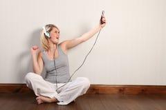 Schönes blondes Mädchen, das zu Hause zur Musik singt Stockfotografie
